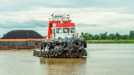 tugboat pull heavy load barge of black coal in Mahakam river, Borneo, Indonesia