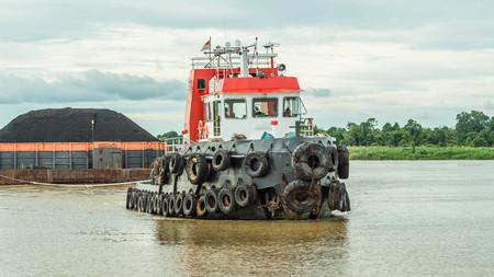 Schlepper ziehen schwere Lastkähne der schwarzen Kohle im Mahakam Fluss, Borneo, Indonesien
