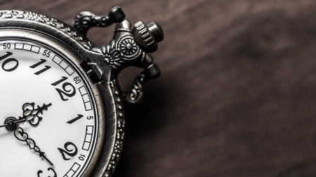old vintage pocket watch showing time with wooden background. time and priority concept