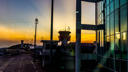 sunset in the airport with terminal building and air traffic controller tower