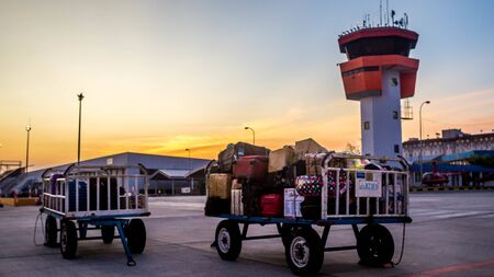 cart of baggage with air control tower as the background Редакционное