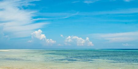 beautiful panorama of horizon with hazy white tropical clouds above tropical blue empty sea. Tranquility of nature