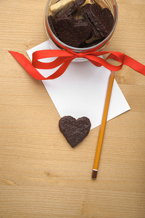 Chocolate cookie-heart on a piece of paper with pencil next to bowl with coffee and red bant