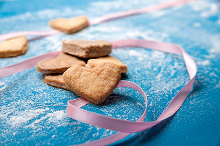Cookie-hearts on a blue with a pink ribbon powdered with a sugar