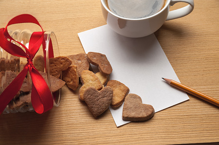 The cup of coffee on the table with a piece of paper, pencil and inverted bowl with cookie-hearts