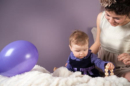 Mother and daughter are having fun together with baloons and jewellery photo