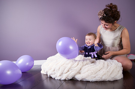 Happy mother and little sweet daughter are laughing together while playing with baloons Stock Photo - 29306333