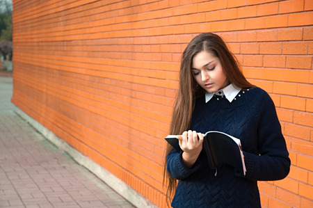 Young woman writes in diary photo