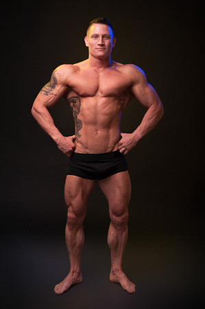 only the biceps: Beautiful physique bodybuilder on a dark background Stock Photo