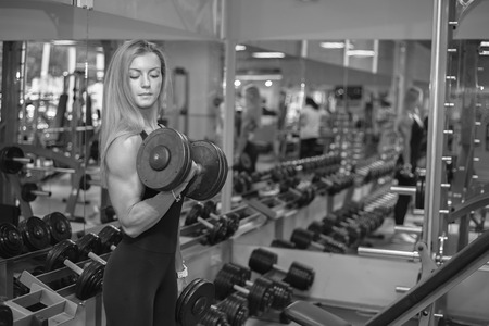 only the biceps: woman shakes her biceps at the gym Stock Photo