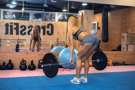 only the biceps: woman shakes her back in the gym
