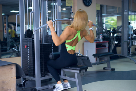 dorsi: beautiful woman trains back in the gym