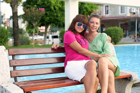 mother on bench: mother and daughter sitting on a bench in the park Stock Photo