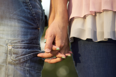 2 persons only: a couple holding hands. Close-up of hands