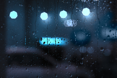 cold background: Rain drops on window with street bokeh lights Stock Photo