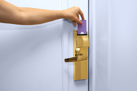 likeable: Young woman holding a keycard in front of the electronic sensor of a room door Stock Photo