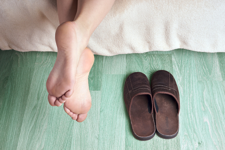 bed feet: female feet and slippers Stock Photo