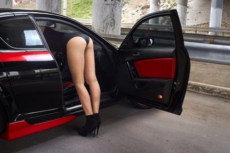 beautiful woman next to sports car