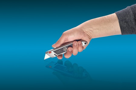 mans hand holding a knife stationery
