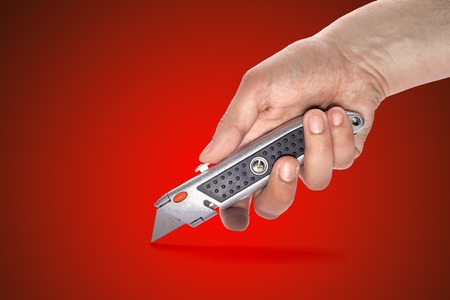 boxcutter: mans hand holding a knife stationery