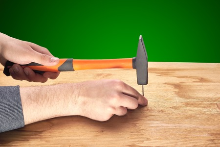 man hammers a nail with a hammer