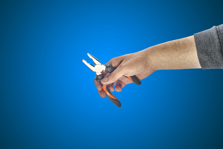 power wrench: mans hand holding a pliers