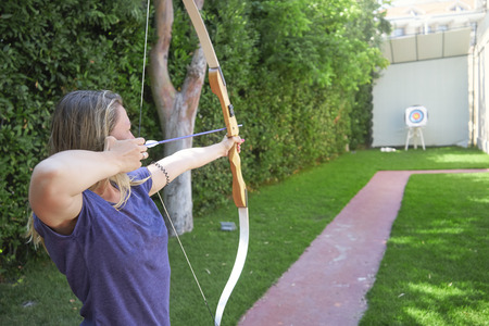 A woman shoots a bow from a target