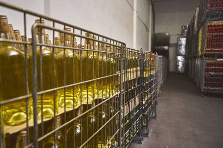 Many bottles are on racks at the winery.