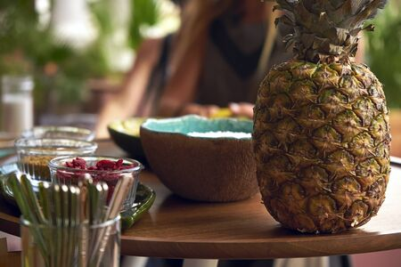 Pineapple stands on a table, along with ingredients for a smoothie bowl