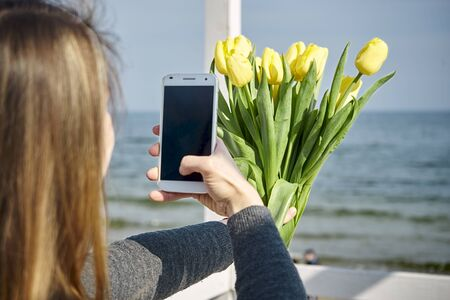 woman photographing yellow tulips against the sea Banco de Imagens