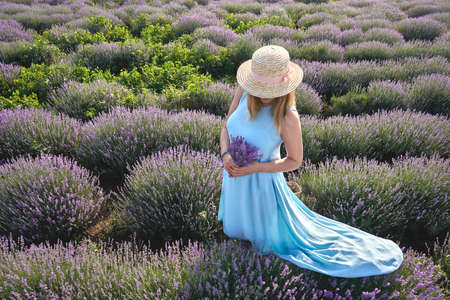 beautiful girl in a straw hat standing in a field of lavender