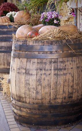 Beautiful ripe orange pumpkin lying in the straw on a wooden barrel Banco de Imagens