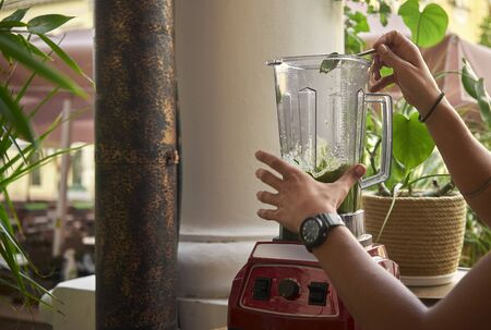 Woman makes a delicious smoothie in a blender Banco de Imagens - 132221584