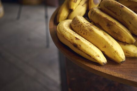 Many tasty and ripe bananas lie on a wooden table. Standard-Bild