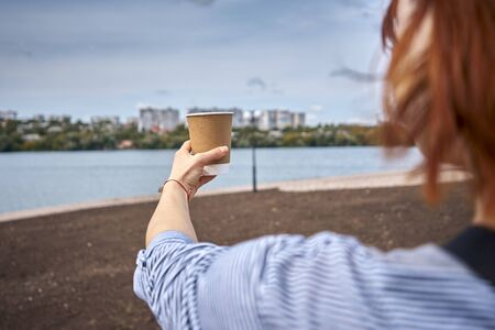 A woman stands with her back outstretched, and in her hand a glass of coffee against the backdrop of a beautiful landscape Banco de Imagens