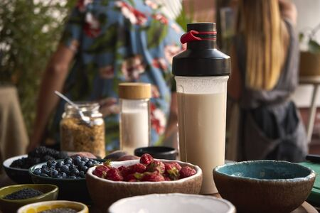 A bottle of almond milk is on the table with fruit Banco de Imagens