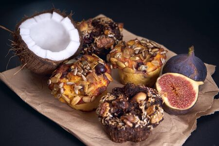 Delicious fresh muffins, and figs, and coconut are on paper