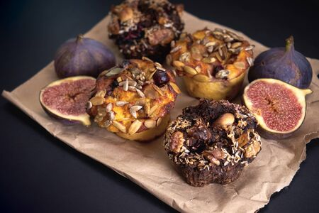 Delicious fresh muffins and figs lie on paper