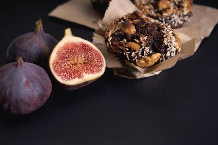 Delicious fresh muffins and figs and hazel lie on the board