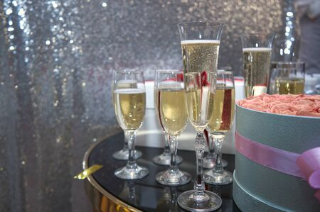 Holiday poured into glasses of champagne, next to it is a bouquet of flowers Banco de Imagens