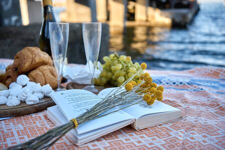 Picnic by the sea. Champagne, flowers, book and delicious food. Banco de Imagens