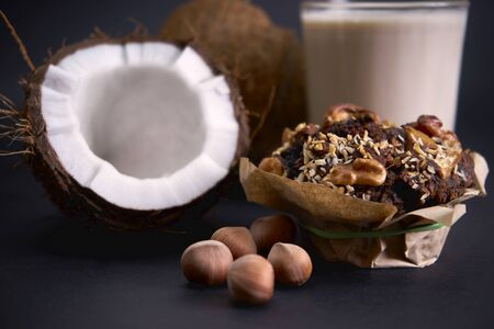 Delicious diet muffins and coconut lie on paper on the table.