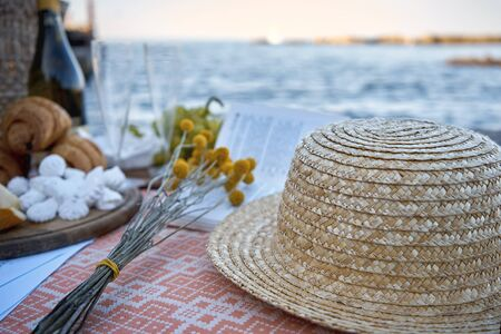 Picnic by the sea. Champagne, flowers, book and tasty food, hat