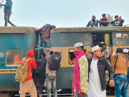Dhaka,Bangladesh-01/11/2020:Bangladesh train/railway -man stuck between two compartment trying to get into train's roof to go to their home districts on a busy crowded train