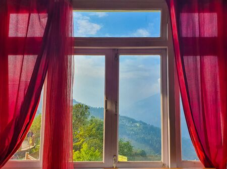 Window of a room with red curtains and a beautiful hill view in the background Reklamní fotografie