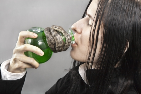 wrongdoing: The pale person drinks poison from a flask Stock Photo