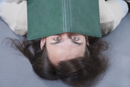 long-haired man lies with book on his face photo