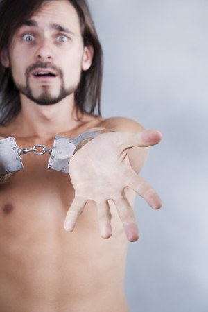 chained in handcuffs long-haired caucasian guy  photo