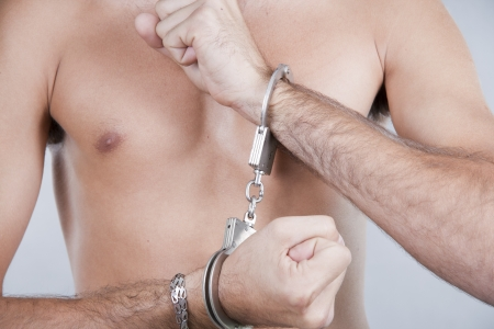close-up mans hands chained in handcuffs  photo