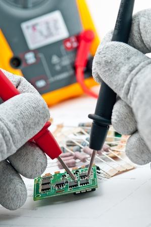ingenieur electricien: V�rification du circuit par Multi-Meter ing�nieur �lectricien � bord lors de la v�rification unit� de carte de circuit imprim� par Multi-Merer Banque d'images